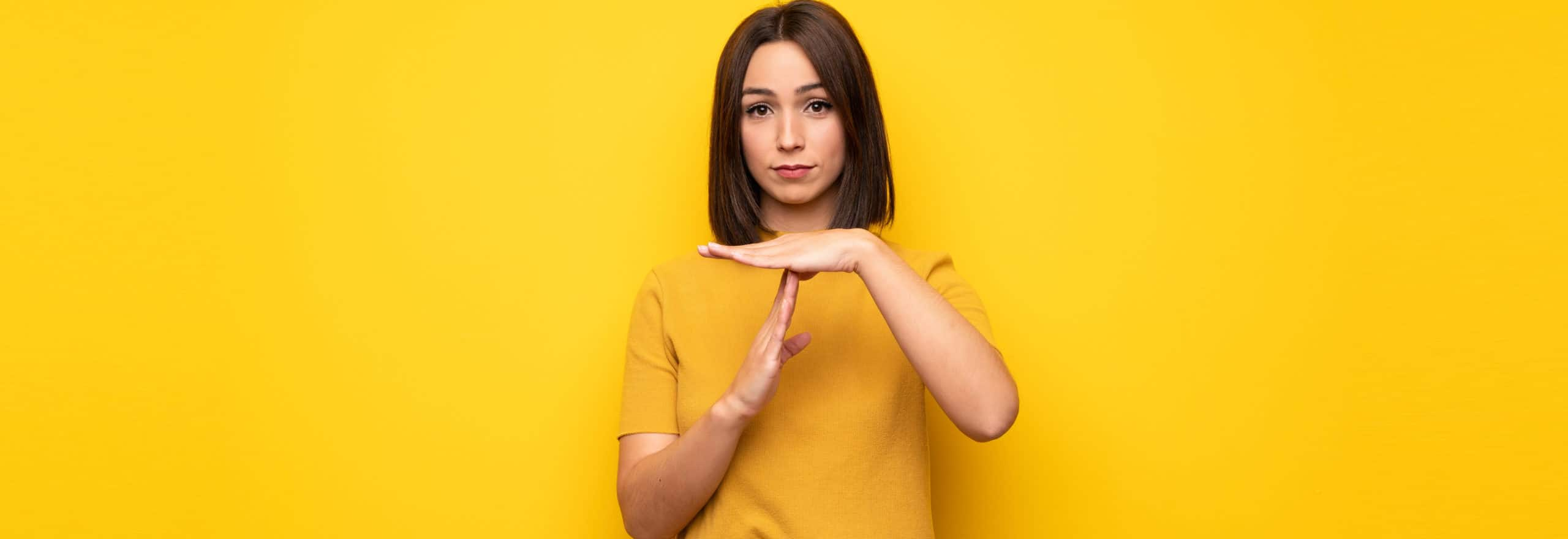 Young woman over yellow wall making time out gesture Von luismolinero